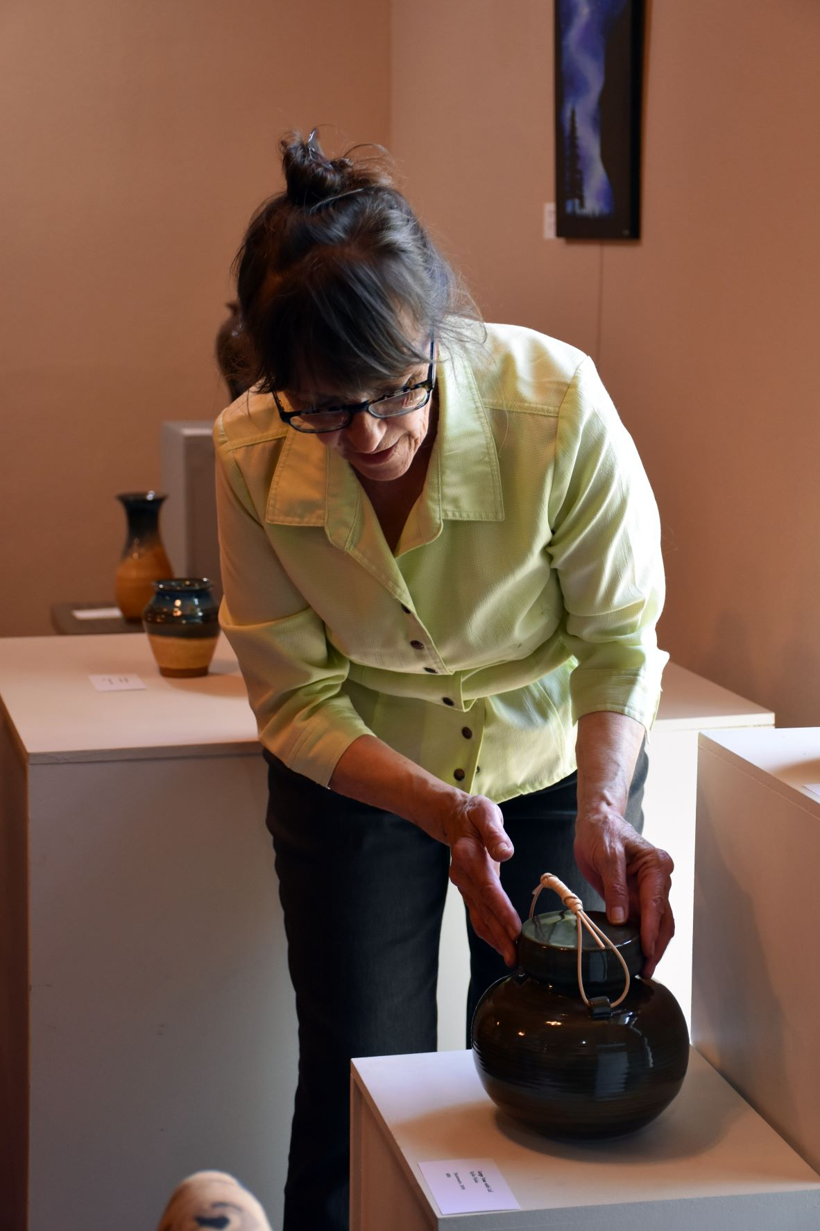 Rosemary setting up pottery exhibit at the Bird Island Cultural Centre.
