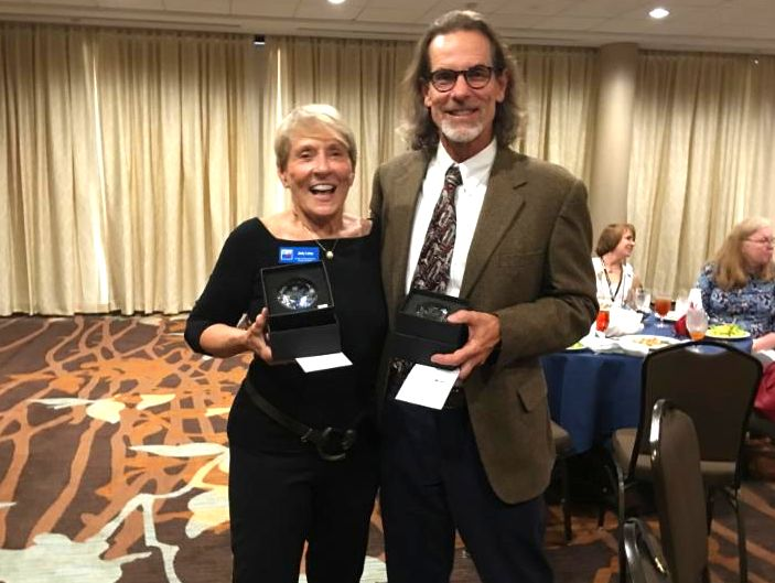 Judy Lotas and Craig Merrill with awards for leading League Action Teams