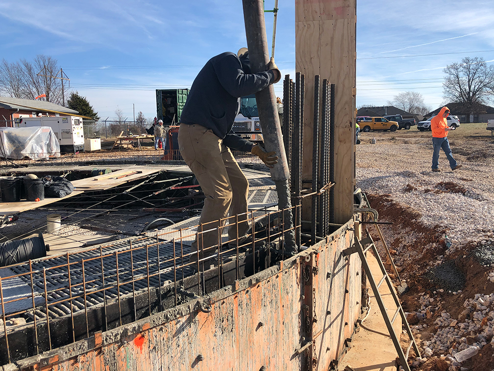 Construction worker pouring concrete for water tower 10