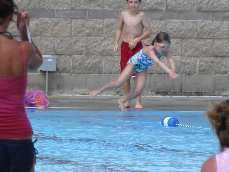 Girl jumping into swimming pool.