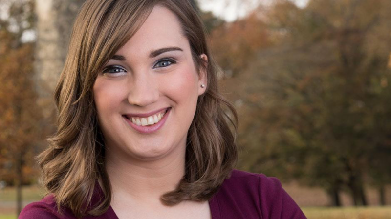 Photo of Sarah McBride, trans activist, smiling at the camera, wearing a plum shirt, with trees in the background.