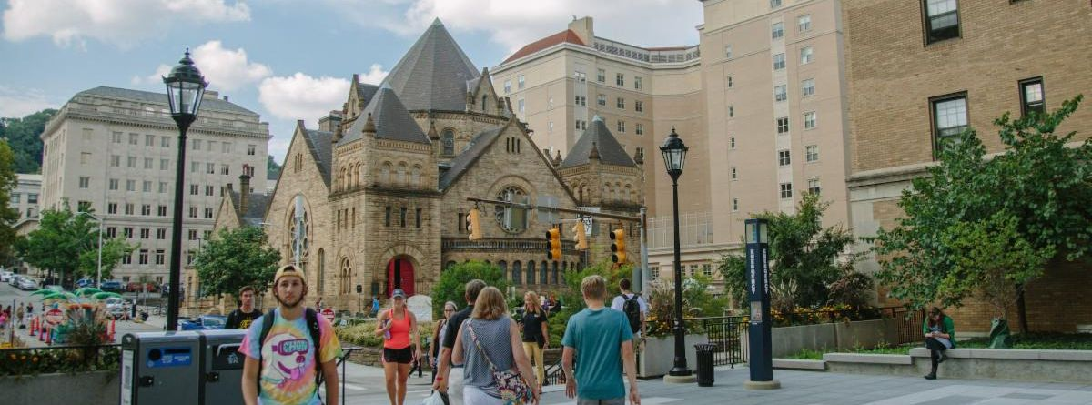 Students walk on the patio of the Towers dorm with Bellefield Church and Nordenberg Hall in the background