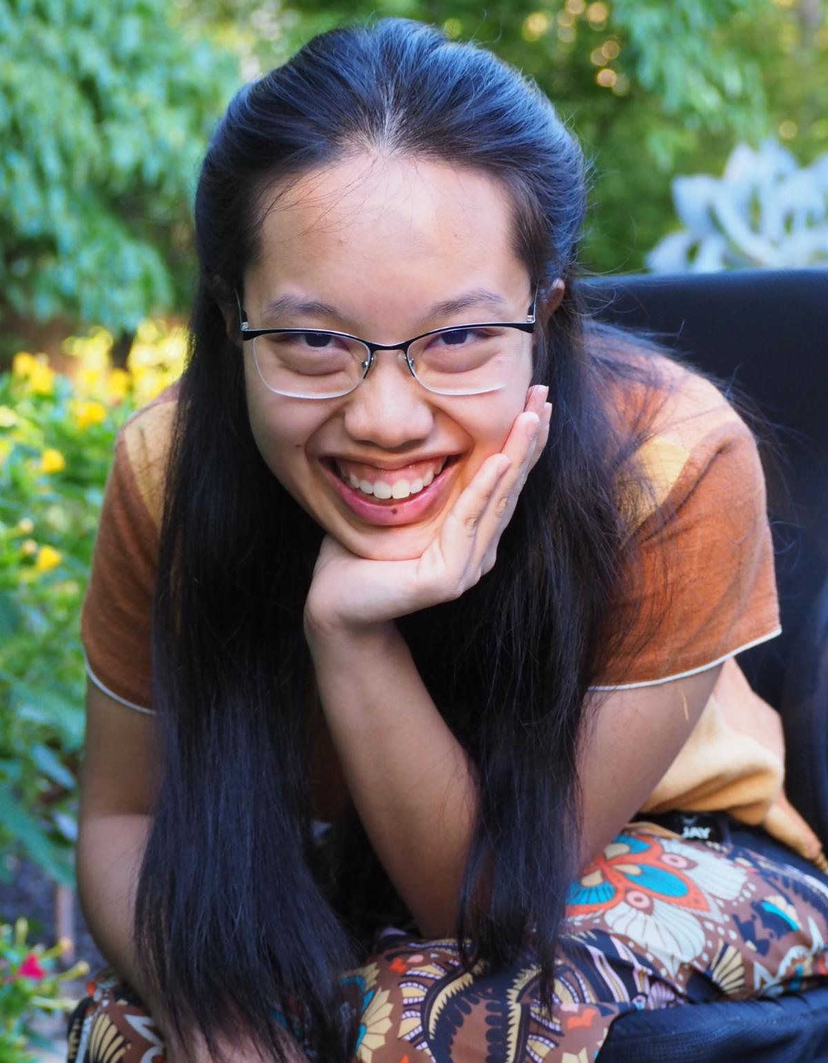 Student spotlight June 2021. Peach is a young woman with long black hair and glasses. In this photo, she is smiling and leaning forward in her wheelchair. She is outdoors. It is a very nice photo.