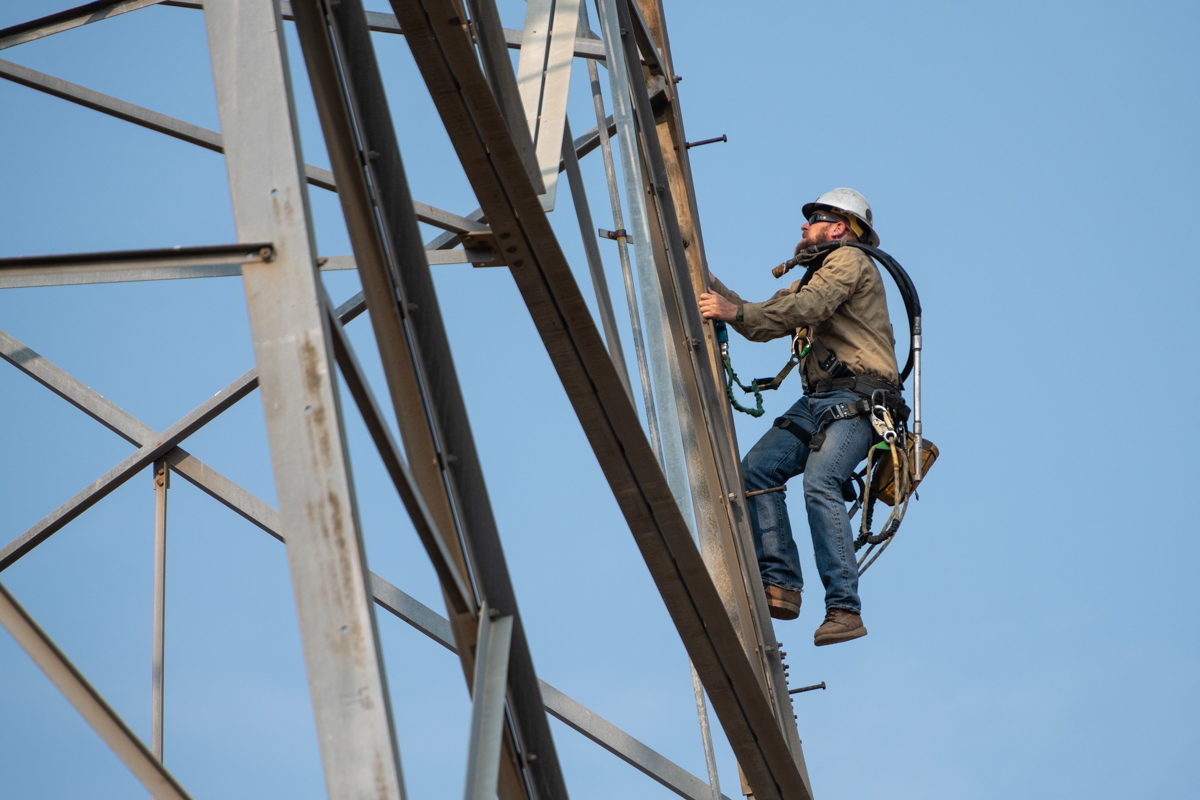 Electrical worker climbing transmission tower.