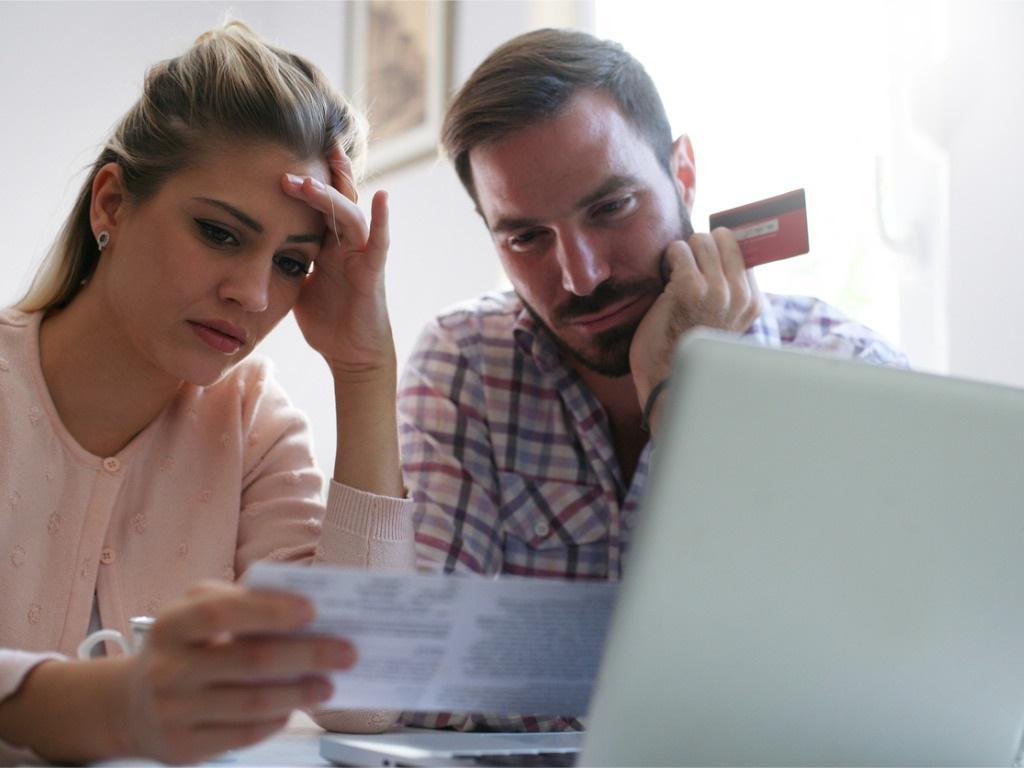 Man and woman reviewing bills at computer