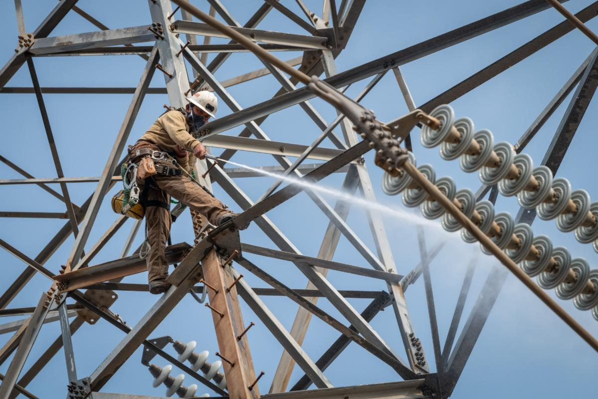 Electrical worker spraying water to clean transmission tower.