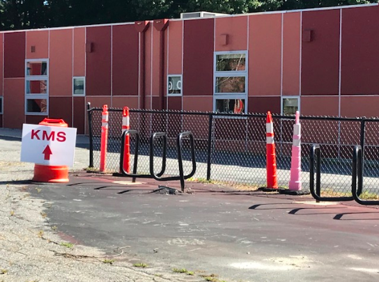 """Brown modulars pictured with """"KMS"""" sign for natvigating the campus during construction in foreground."""