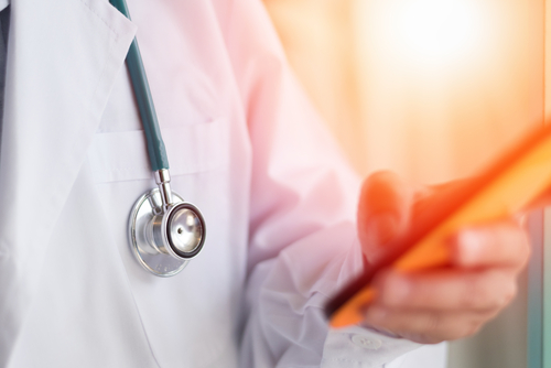E-Health Doctor. Professional medical physician hand holding smartphone connecting with patient consulting in clinic hospital. Medical  healthcare  technology concept
