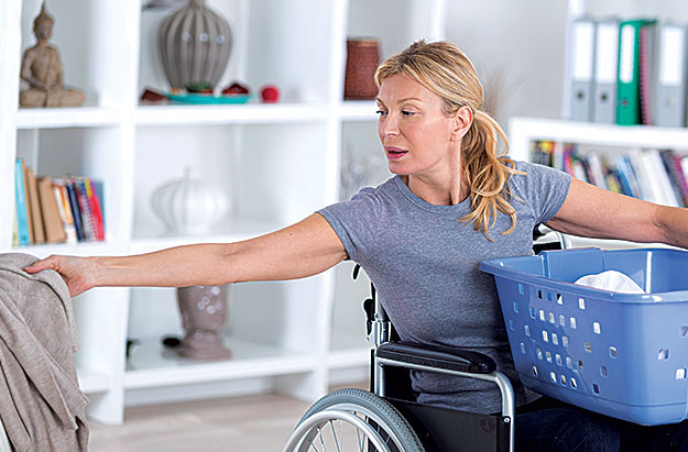 A woman in a wheelchair carrying a laundry bin