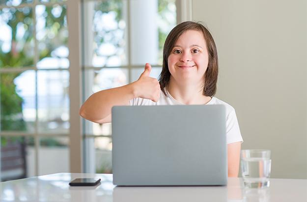 A smiling woman sitting at a table behind a laptop giving a thumbs up