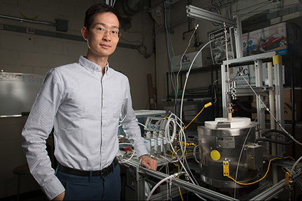 XiaoYu Wu pictured with the reactor his team used for the research. MIT researchers have developed a new system that could potentially be used for converting power plant emissions of carbon dioxide into useful fuels. Image, Tony Pulsone