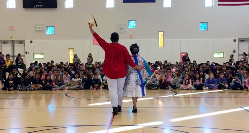 Photo of folkloric dancers performing during an assembly at W.A. johnson School