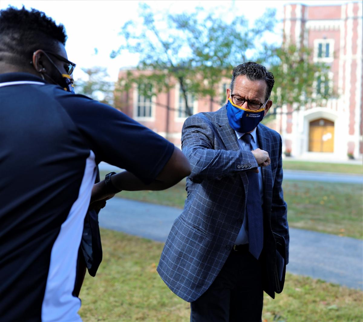 Chancellor Malloy bumping elbows with a UMS student graphic image