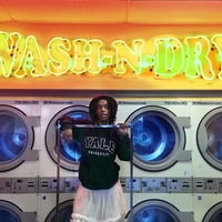 TJ Dedeaux Morris stands in front of a row of washing machines with a neon sign above reading Wash N Dry