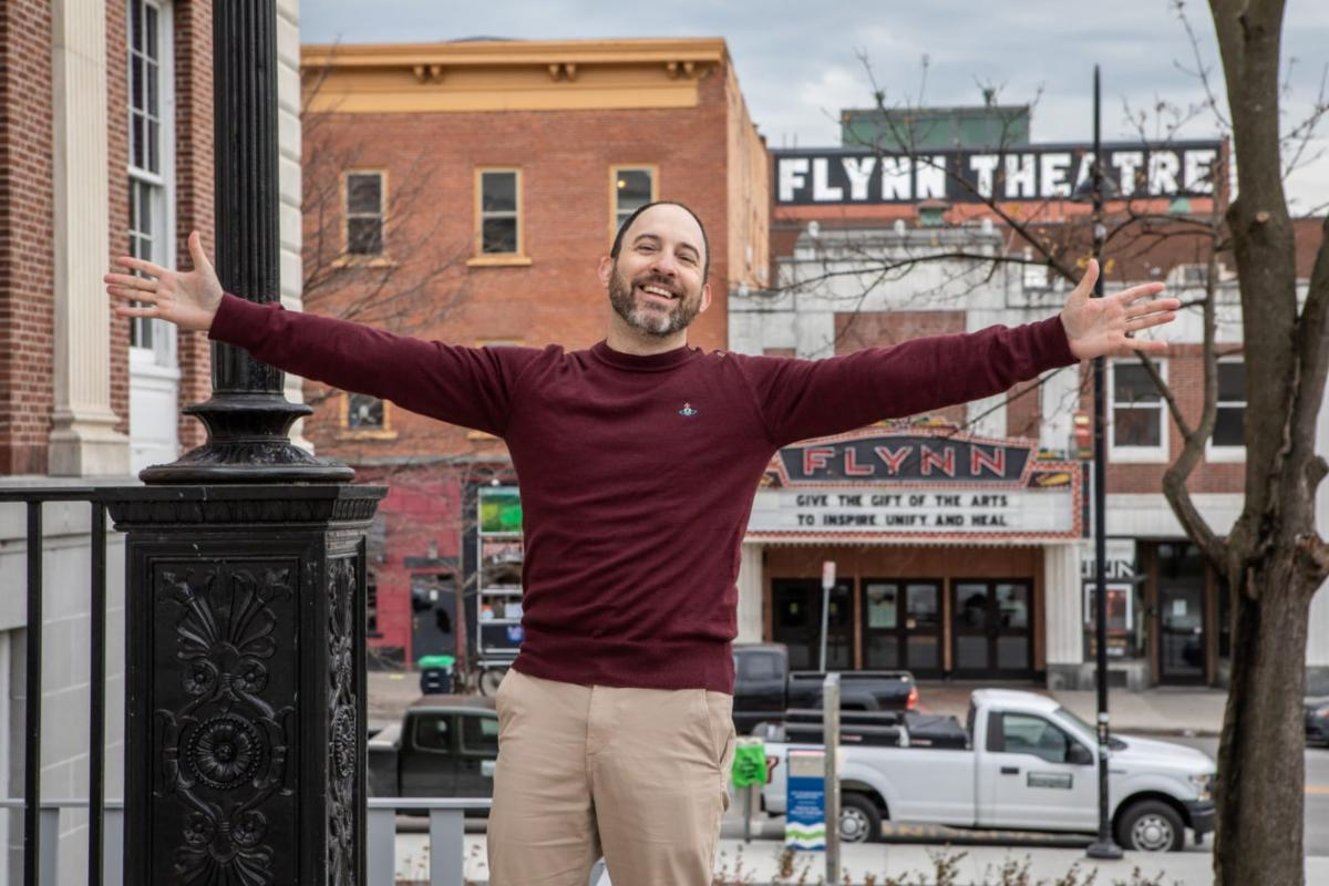Jay Wahl stands with arms wide open on the street in Burlington in front of the Flynn