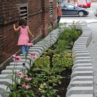 Child walking on stone pathway next to brick building in Barre.