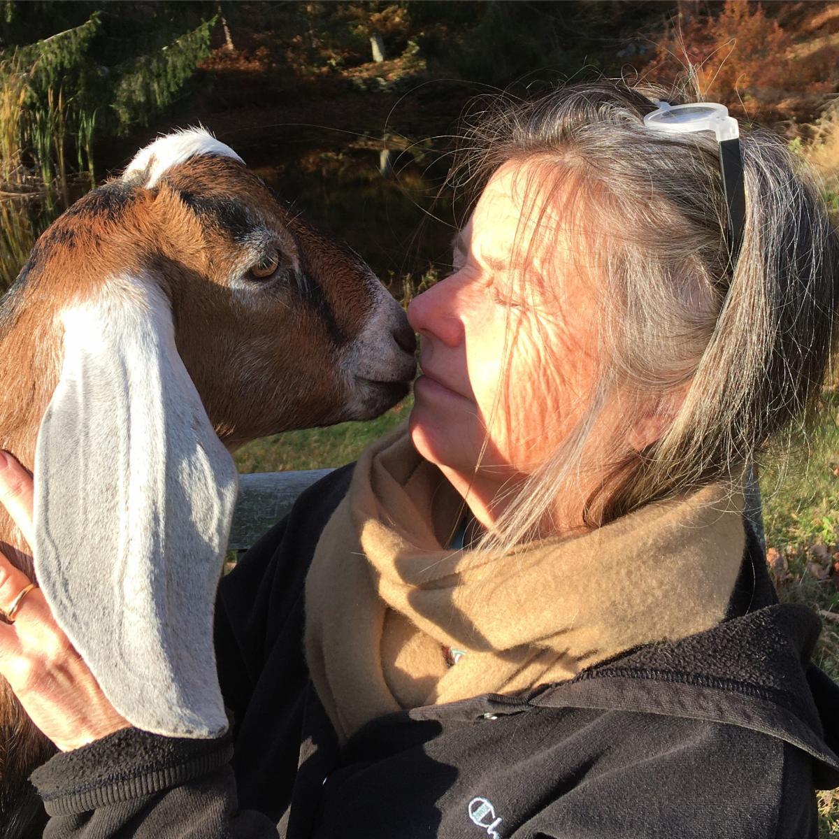 Dona Ann McAdams nuzzling a goat