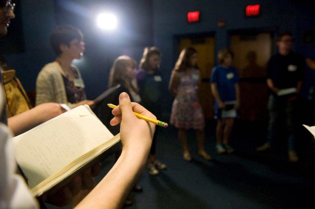 Someone holds a pencil over a notebook in a room full of people wearing nametags