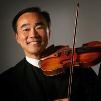 Violinist Cho Liang Lin smiling at the camera with his violin at his chin