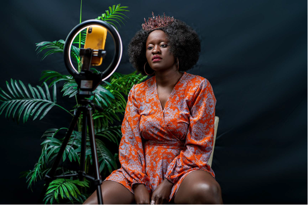 A black woman in a floral dress sits before a ring light and phone and beside a large fern