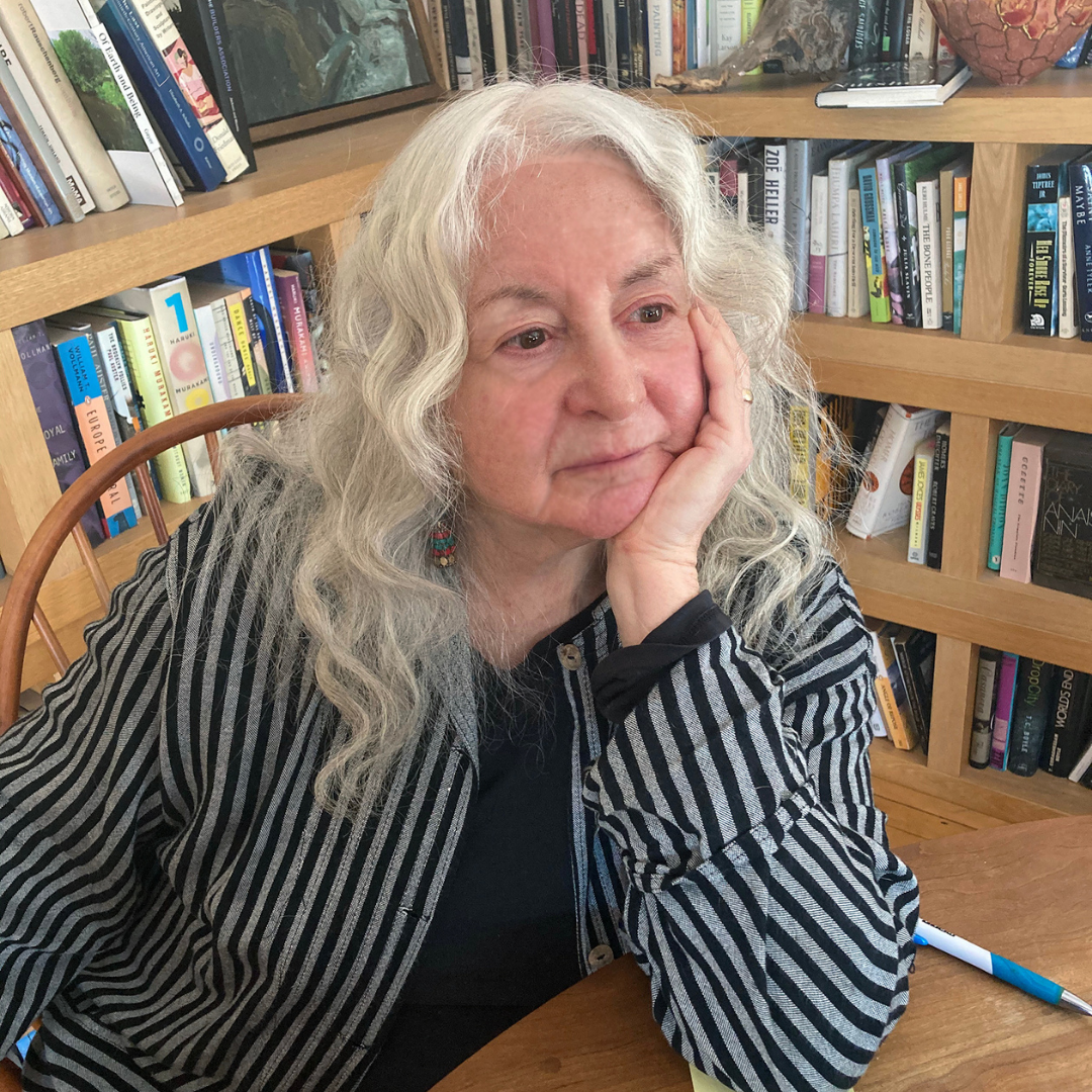Riki Moss sitting at a table and resting her chin in her hand as she looks off camera with bookshelves behind her