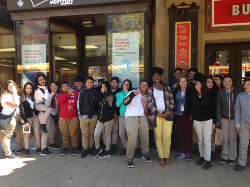Buck Lodge Middle School students sitting in front of store fronts
