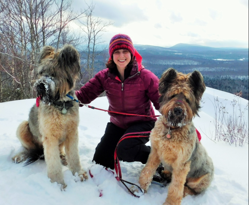 Kristin Caluroso sitting on mountain with two dogs
