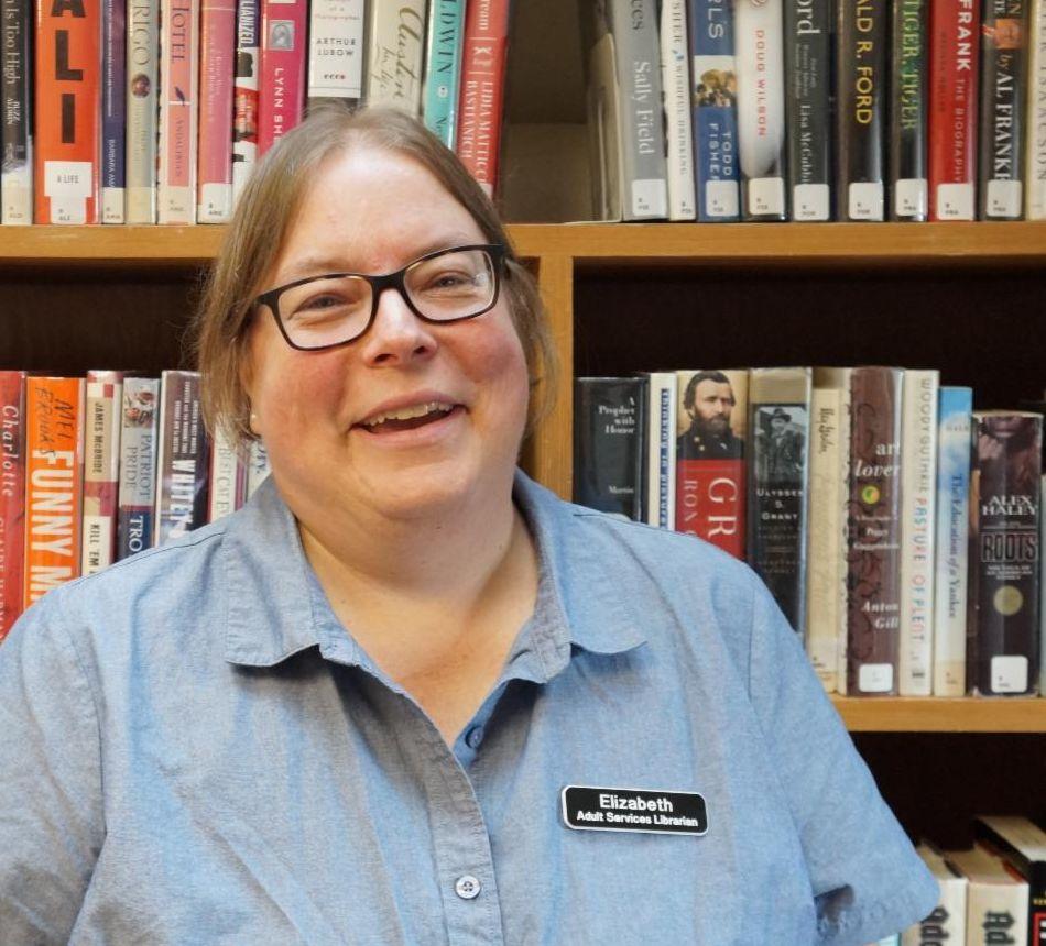 Elizabeth Weilbacher standing in front of book shelves.