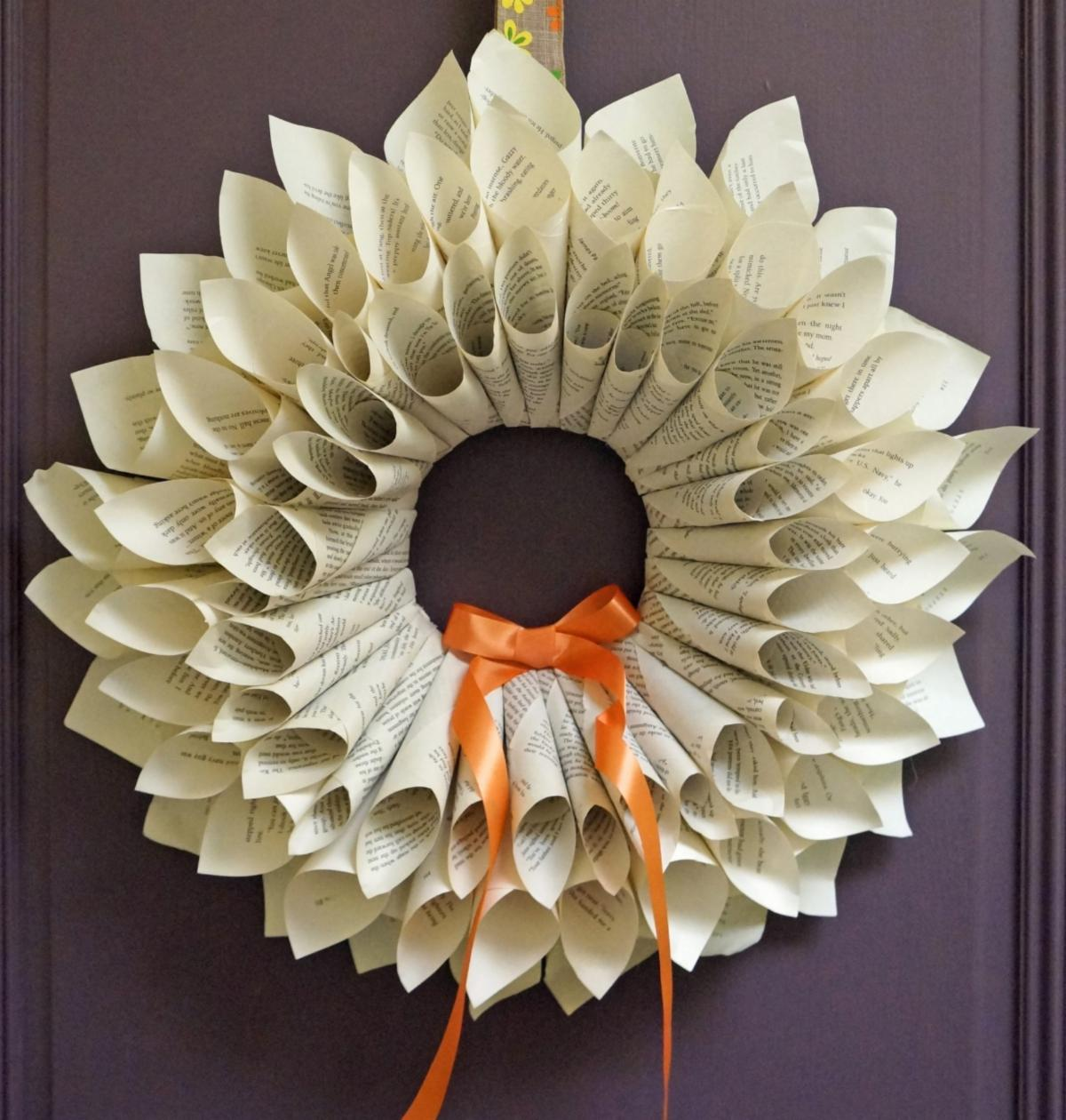 Wreath crafted with rolled book pages adorned with orange ribbon