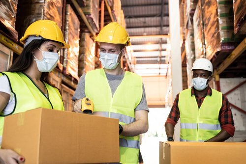 Group of diversity worker wear safety helmet and mask working in warehouse. Woman holding storage box parcel while man standing next to her scanning bar code for quantity count during covid19 pandemic