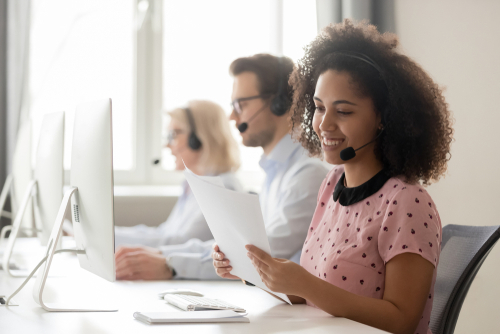 Smiling african american businesswoman call center operator agent wearing headset holding papers reading clients contacts working in customer service support helpdesk business office with colleagues