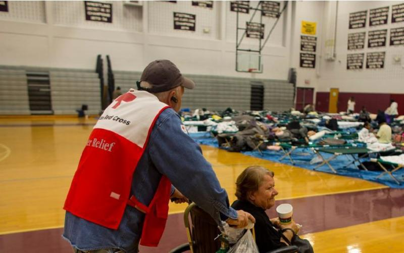 man in red cross vest pushes elderly woman in wheelchair in disaster shelter with cots in background