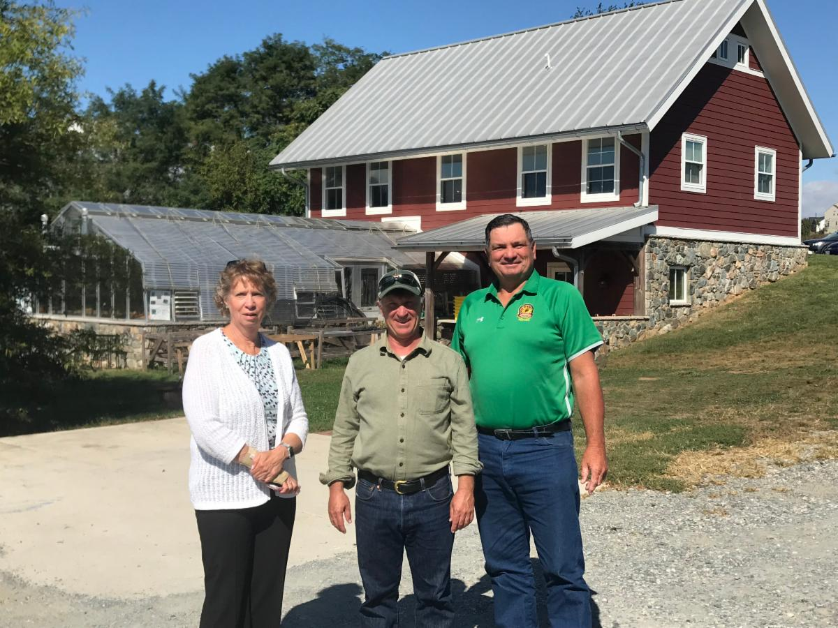 Sec Beatty stands with Sec Bartenfelder and Director Woodson in front of red barn.