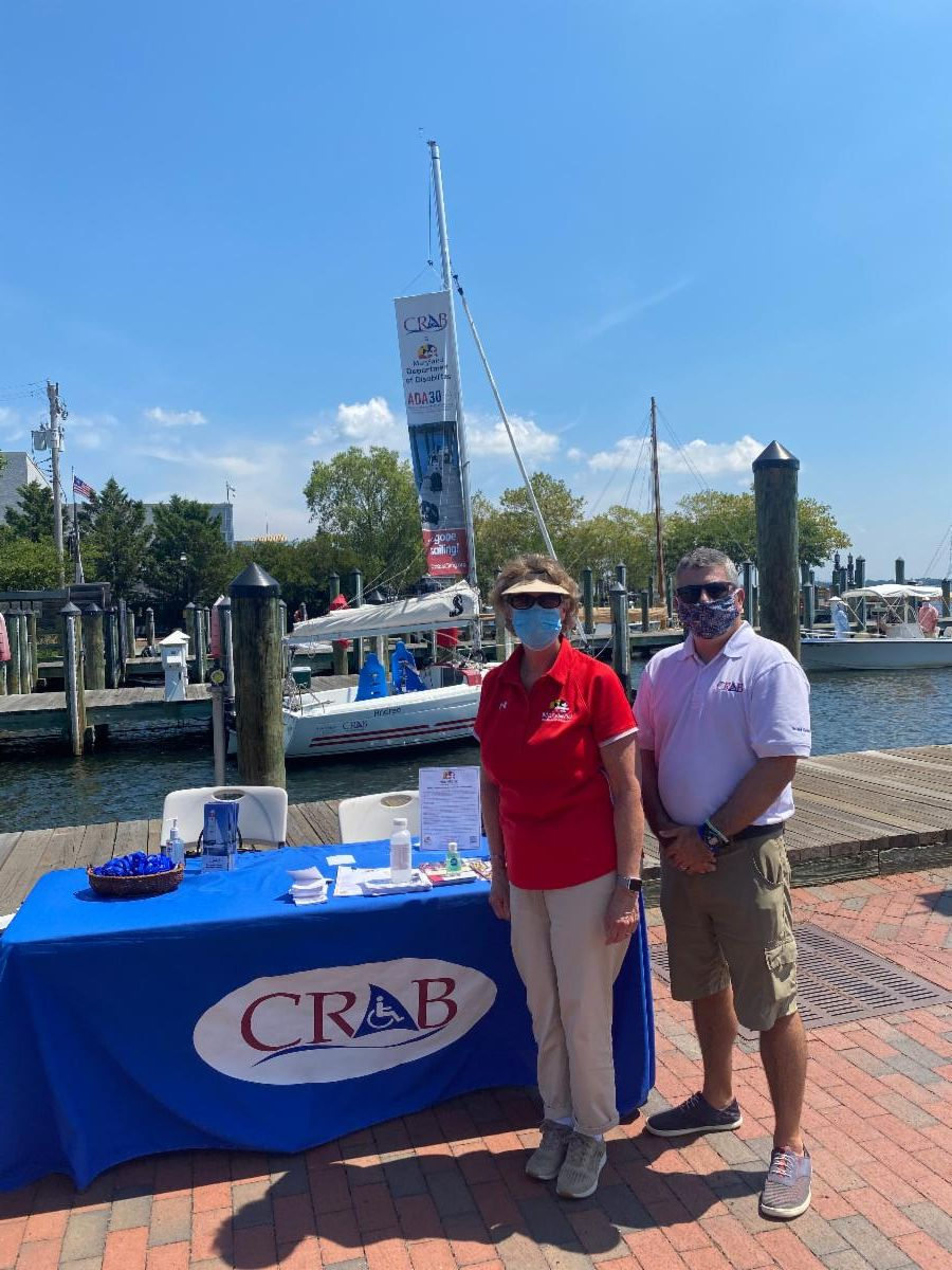 Secretary Beatty stands with CRAB president next to table with blue tablecloth and brochures at Annapolis city dock.
