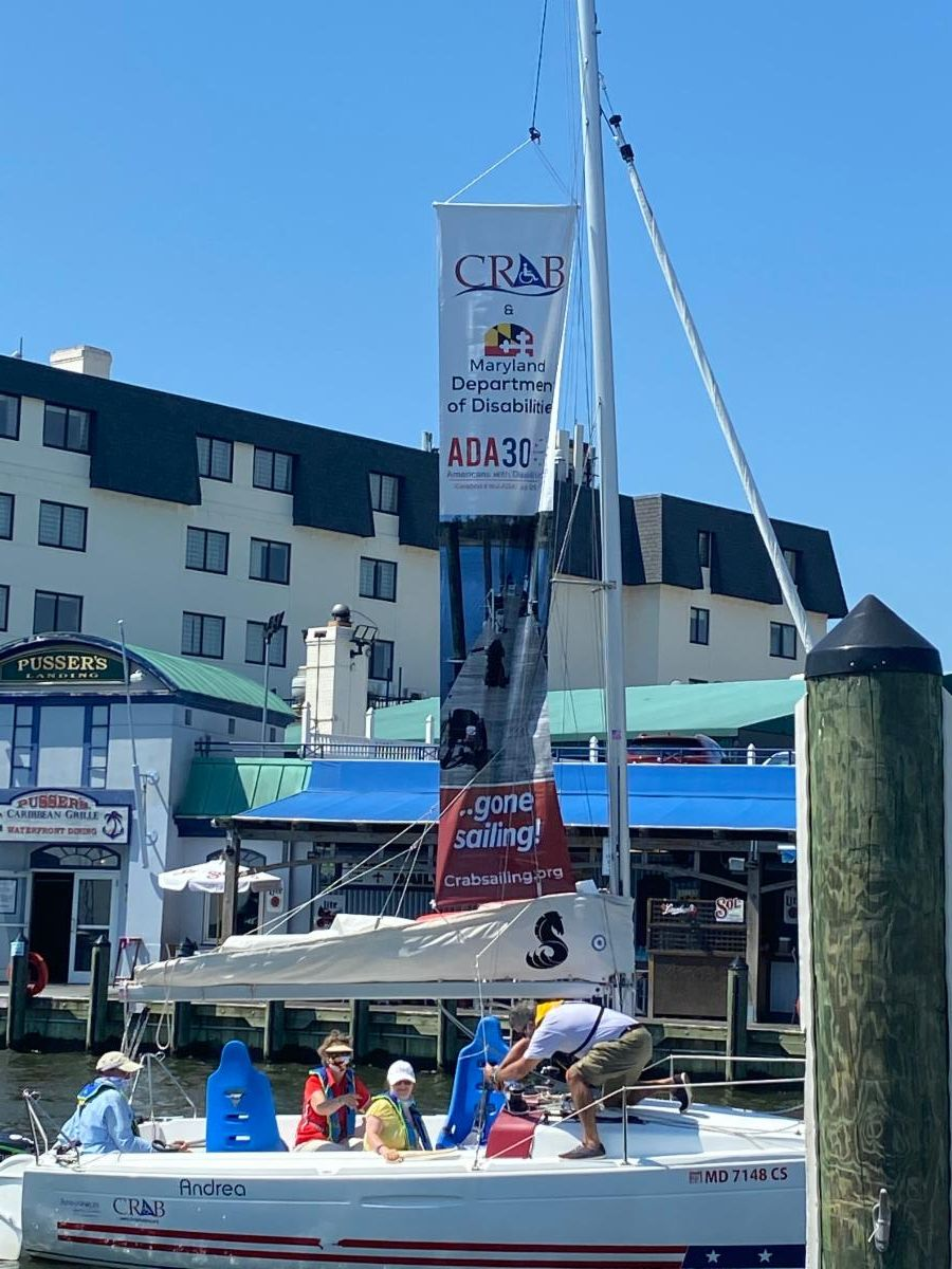 CRAB sailboat in in Annapolis harbor with banner on mast says _CRAB_ MD Department of Disabilities and ADA 30th.