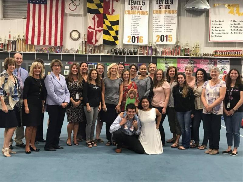 group shot at a gymnastics studio with young child in front