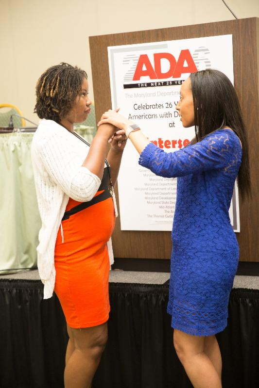 Haben Girma and event attendee communicate with tactile sign