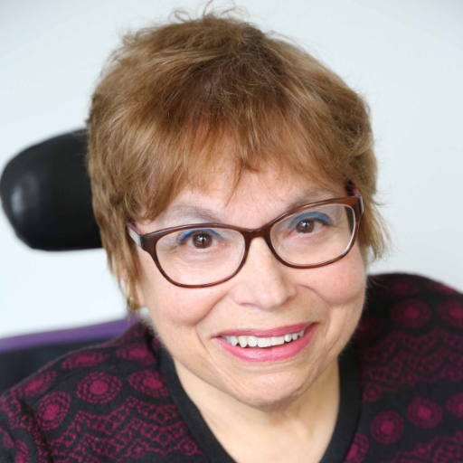 Head shot of Judy Heumann.  She is wearing pink and black shirt and glasses.