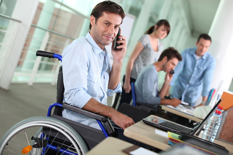 Man in wheelchair on computer and telephone with office workers in background