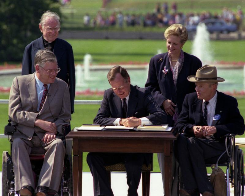 President Bush signs law with four advocates watching him.