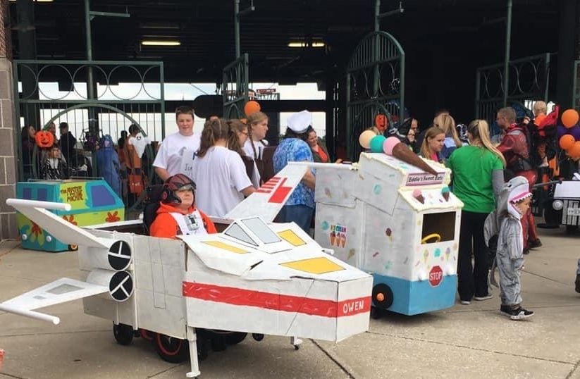 Kids in wheelchair costumes including Star Wars XWing fighter and ice cream truck outside Ripken Stadium.