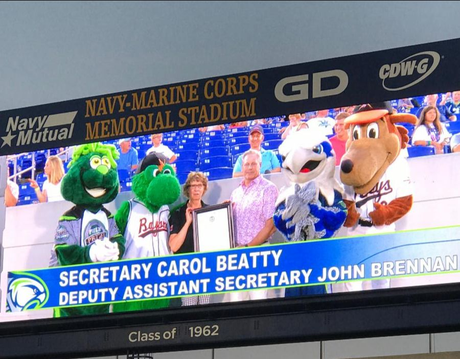 Sec Beatty and Dep Asst Sec Brennan are on Jumbotron holding Governor_s Proclamation.  They are surrounded by 4 local team mascots.