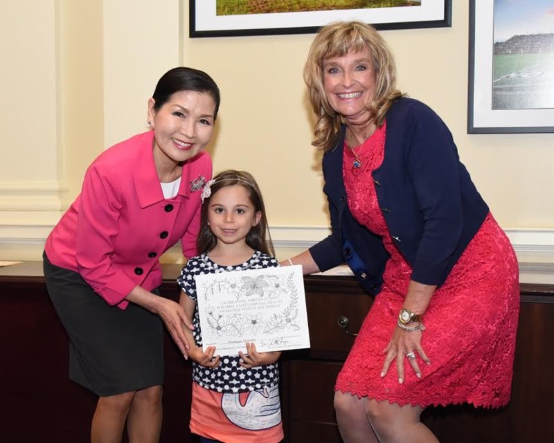 little girl posing with first lady and other woman