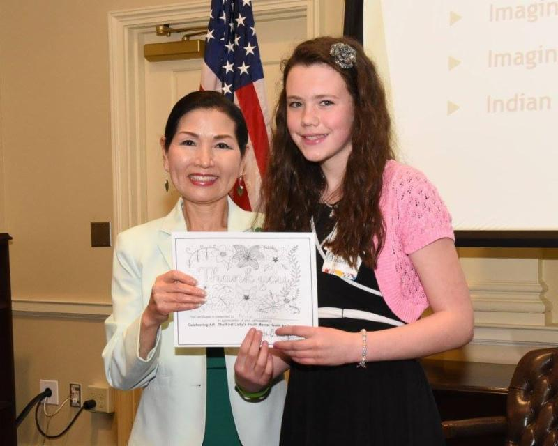 First Lady poses with young girl and certificate