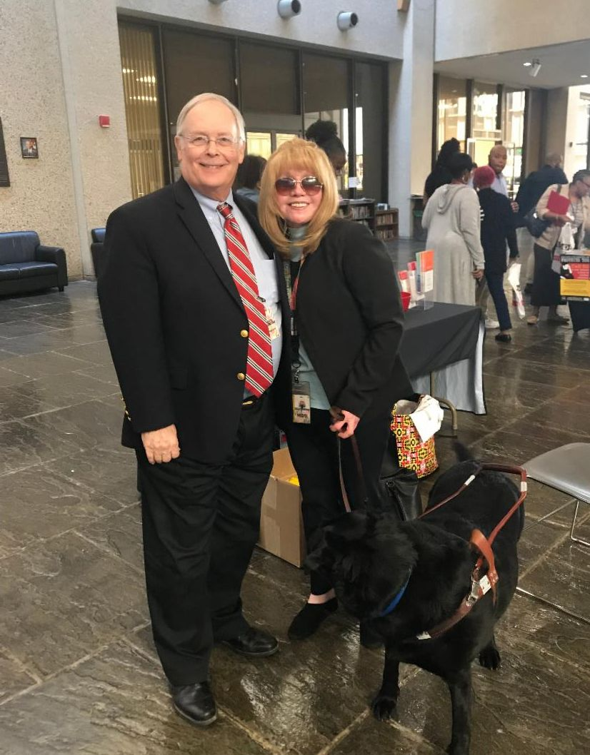 MDH Secretary Robert Neall stands with Emergency Prep Director Cecilia Warren and her guide dog Yale.