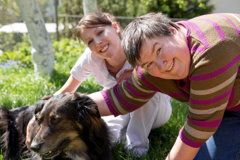 man and woman smile into the camer and pet dog