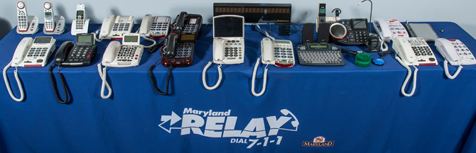 Long table with 20 different kinds of telephones on a blue tablecloth with MD relay Dial 7-1-1 logo.