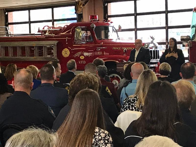 Governor Hogan addresses full crowd in foreground with fire trucks in background