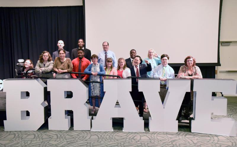 group standing behind letters spelling brave