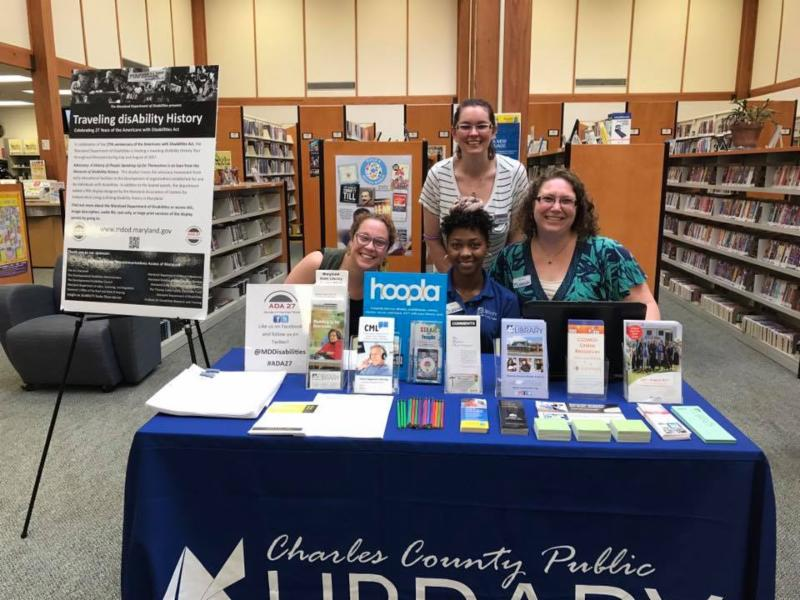 Group of librarians pose in front of Charles County library table